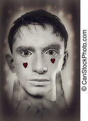 man with white makeup and red hearts on face