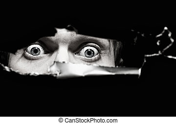 Scary eyes of a man spying through a hole in the wall close...