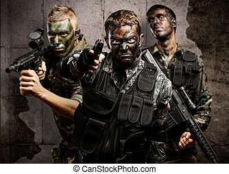 group of soldiers aiming with rifles against a grunge bricks...