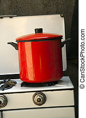 cooking pot on old kitchen - single red pot on an old cooker