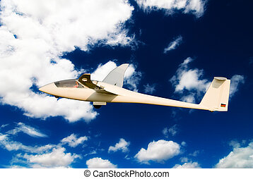 glider - little glider over blue sky and clouds background