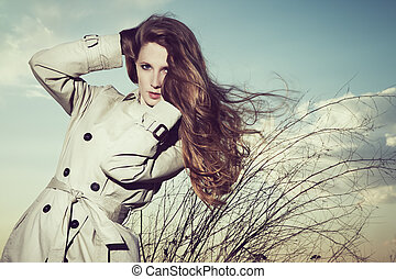 Fashion portrait of elegant woman in a raincoat on the...