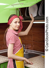 Woman in kitchen interior with clean plates - Woman in...