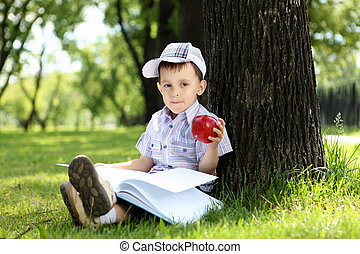 Portrait of a boy with a book in the park