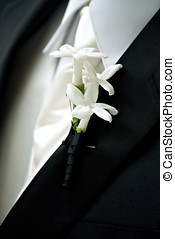 Groom in black wedding suit wearing a white Boutonniere -...