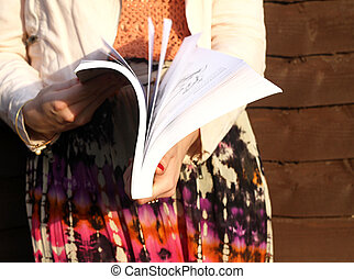 book flipping - a young woman poses whilst flipping through...