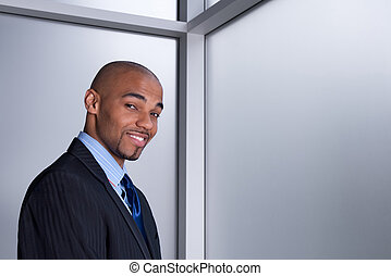Smiling businessman beside a window