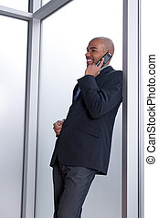 Businessman leaning against the window, talking on the phone...