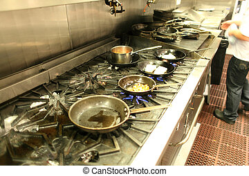 Restaurant kitchen with pans on the stove.