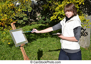 Charming artist in a park - Pretty female artist drawing...