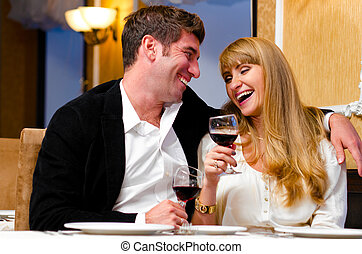 couple at restaurant - laughing embracing couple is sitting...