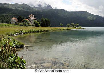 clear water and castle, engadin - high mountain landscape in...