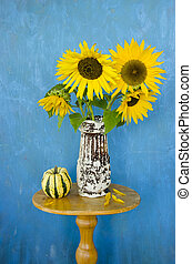 still-life with retro vase and sunflowers on blue background