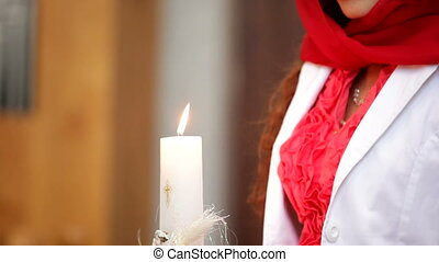 Girl holds a candle - A woman prays in a church holding a...