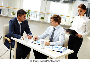 Financial briefing - Office workers discussing financial...