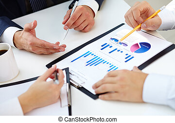 Charts and graphs - Hands of business people over documents...