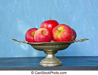 vintage vase and red apples on blue background