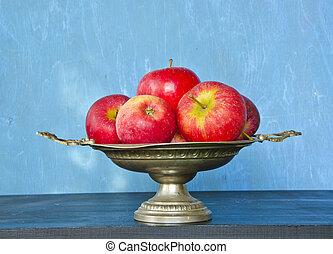 vintage vase and red apples on blue background