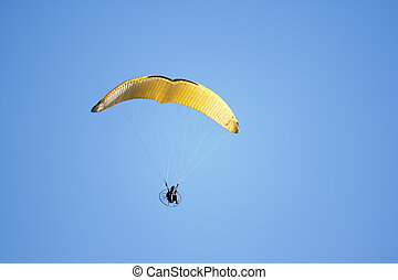 paragliding - A Paraglider flies against blue sky background