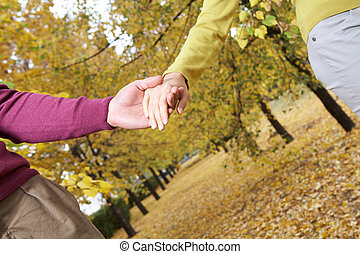 Walking couple - Linked hands of couple walking in autumn