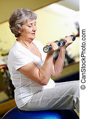 Low weight - Senior women lifting dumbbells in gym