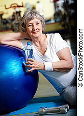 Break in gym  - Senior woman having break after exercises