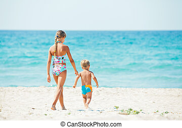 Young girl and boy playing happily at pretty beach - Young...