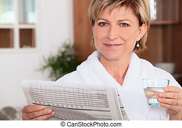 Woman drinking water whilst reading newspaper