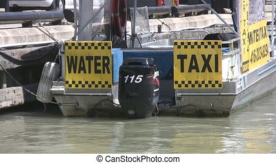Water taxi. - A water taxi boat tied to a dock. Two shots....