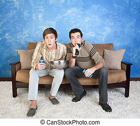 Friends Watch Television - Two young Caucasian friends with...