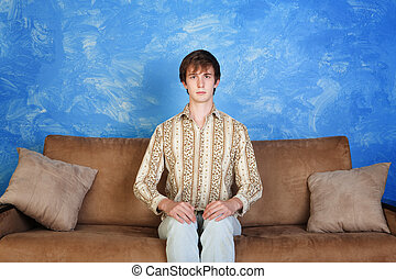 Stiff Young Man on Sofa - Young Caucasian man sits straight...