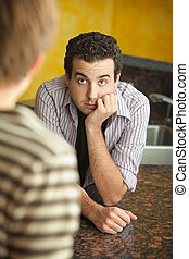 Young man in kitchen with friend - Worried young Caucaisian...