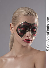 pretty blonde with carnival mask painted on face