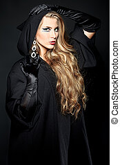 horror - Charming halloween witch over black background.