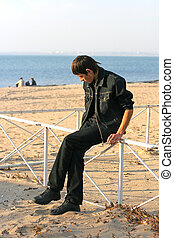 sad young man on the empty beach