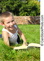 kid with a book - The happy child with the book lays on a...