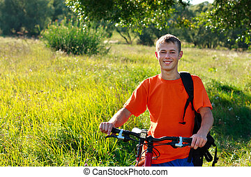 Smiling man cyclist among the green scenery