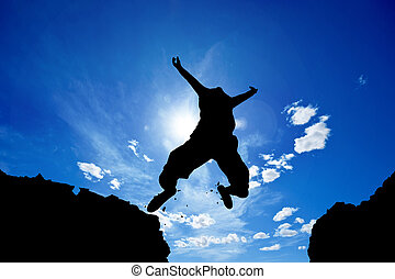 jumper - man jumping from a cliff over vivid blue sky