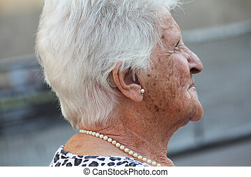 old lady with a hearing aid - portrait of an old lady with a...