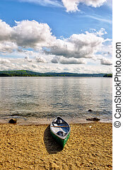 Green canoe on lake shore - A green canoe on the shore of...