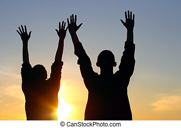 praying people - young couple hands up silhouette