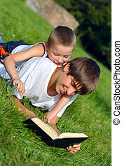 teenager and kid with a book - The happy teenager and kid...