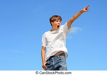 pointing teenager - amazed teenager pointing on blue sky...