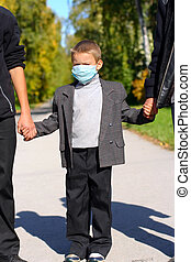 kid in the flu mask on the street with two persons