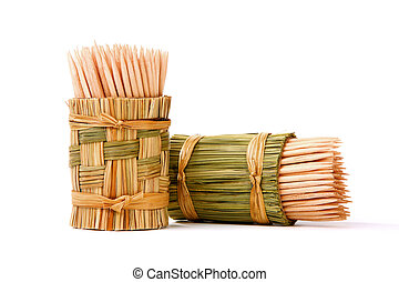 wooden toothpicks in a stand of straw on a light background
