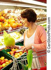 Woman in supermarket - Image of senior woman choosing...