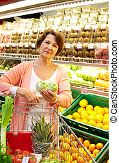 Woman with goods - Image of senior woman in groceries...