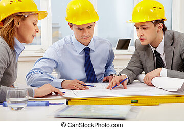 Architects at work - Three architects sitting at table and...