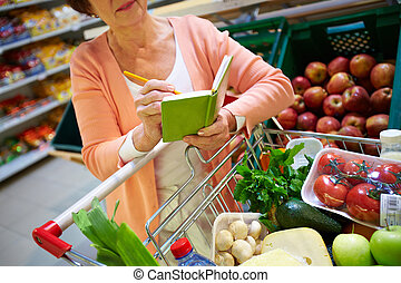 Shopper with notepad - Image of senior woman looking at...