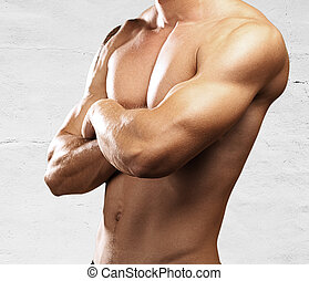 strong torso of young man against a stone wall